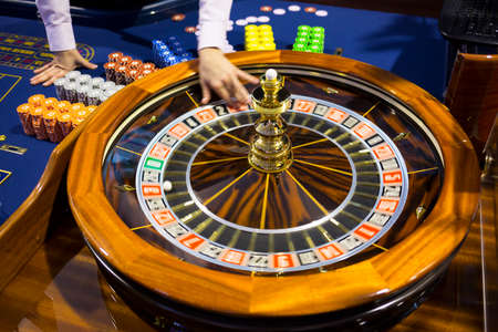 Roulette table in casino. Ball in the rotating gambling machine. Wooden roulette wheel. Casino croupier releases roulette white ball.