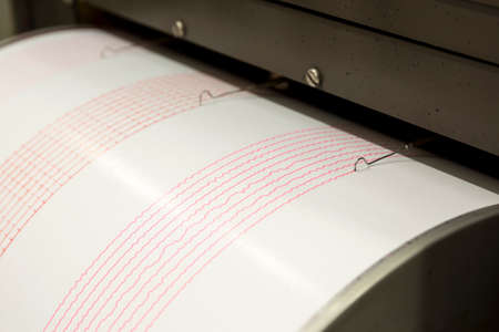 sismográfo: Seismograph records an earthquake on the sheet of measuring paper. Seismological device for measuring earthquakes. Seismograph machine needle drawing a red line on graph paper measuring activity.
