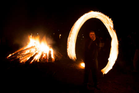 Lozen, Bulgaria - 26 February, 2017: A boy spins rings of fire near a bonfire during a fire ritual celebration of Sirni Zagovezni held seven weeks before Easter. People beleive they chase away evil spirits with fire rituals.