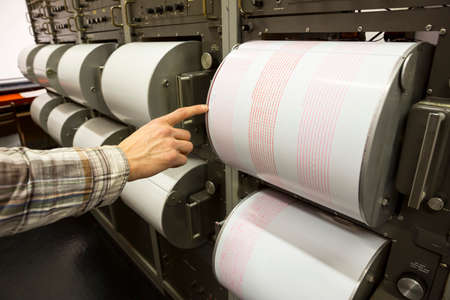 Seismograph records an earthquake on the sheet of measuring paper. Seismological device for measuring earthquakes. Earthquake wave on graph paper. Human finger showing a detail of the earthquake.