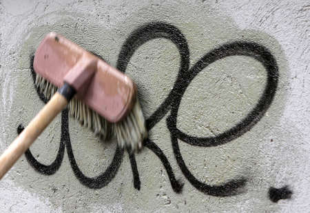 Cleaning graffiti with a brush.