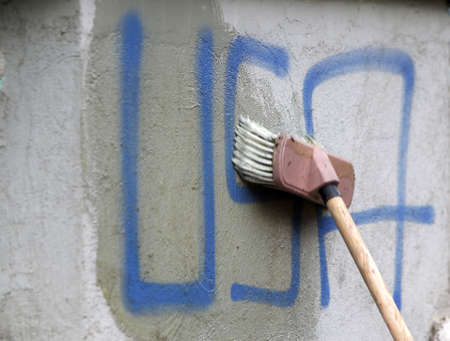 cleaning service: Cleaning graffiti with a brush.