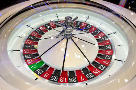 Modern roulette table in casino. Ball in the rotating gambling machine. Colourful roulette wheel. Stock Photo