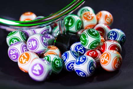 Colourful lottery balls in a bingo machine. Lottery balls in a sphere in motion. Gambling machine and euqipment. Blurred lottery balls in a lotto machine.