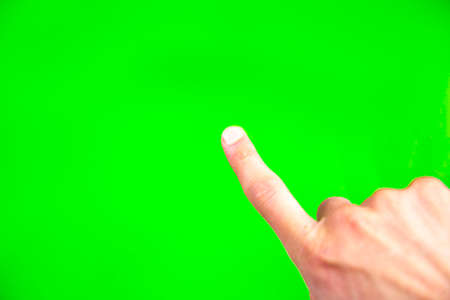 Young man types and slides on a computer screen. Digital screen with chroma key screen - green screen. Male hand. Stock Photo