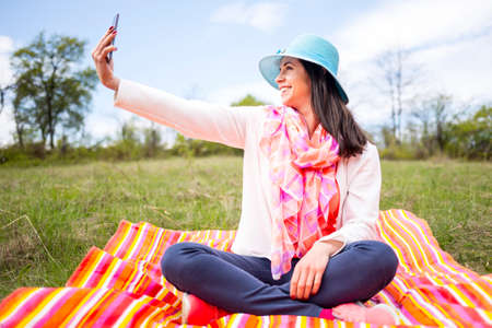 Attractive smiling young woman dressed casually takes a selfie sitting on a colourful blanket in the park. Modern lifestyle using portable mobile devices everywhere people go. Photo of yourself.