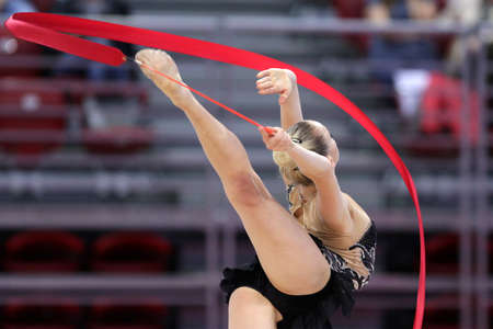 Individual Rhythmic gymnastics athlete performs with ribbon on the arena. Unrecognizable people.