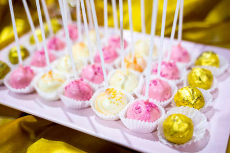 Different colourful candies on a stick. Bonbons wrapped in golden foil. Yellow, pink, white. Extremely tasty and delicious desserts. Sweets full with sugar. Unhealthy food diet.