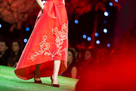 A female model walks the runway in a beautiful red dress during a Fashion Show. Fashion catwalk event showing new collection of clothes.