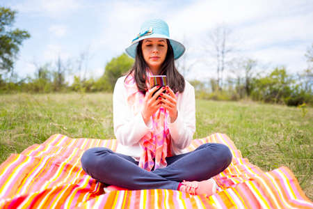 Attractive young woman dressed casually uses smartphone sitting on a colourful blanket in the park. Modern lifestyle using portable mobile devices everywhere people go. Texiting sms.