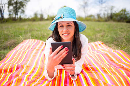 Attractive smiling young woman dressed casually uses e-book/tablet lying down on a colourful blanket in the park. Modern lifestyle using portable mobile devices everywhere people go. Reading e-mail.