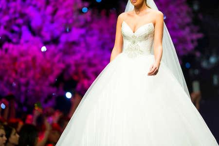 女性モデルは、ファッションのショーの間に美しいスタイリッシュな白いウェディング ドレスで滑走路を歩きます。ファッションショーのキャット