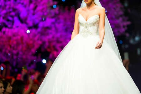 A female model walks the runway in beautiful stylish white wedding dress during a Fashion Show. Fashion catwalk event showing new collection of clothes.