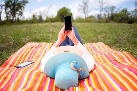 Young woman with blue hat dressed casually uses smartphone lying down on a colourful blanket in the park. Modern lifestyle using portable mobile devices everywhere people go. Texiting sms. Stock Photo