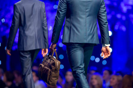 A male model walks the runway in stylish blue suit holding brown bag during a Fashion Show. Fashion catwalk event showing new collection of clothes. From the back of the model.