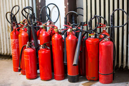 extinguishing: Many red fire extinguishers on the ground. Foam, Carbon dioxide, Powder and Water. Stock Photo