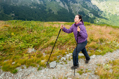 Young woman hikes up a rocky mountain hill with trekking canes. Cold temperature. Purple jacket and black bottoms.