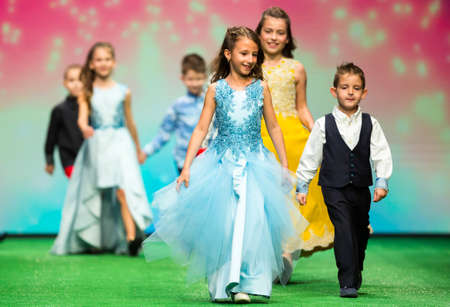 Sofia, Bulgaria - 21 March 2017: Children models walk the runway during the Sofia Fashion Show. Fashion catwalk event showing new collection of clothes. Girl in blue dress.