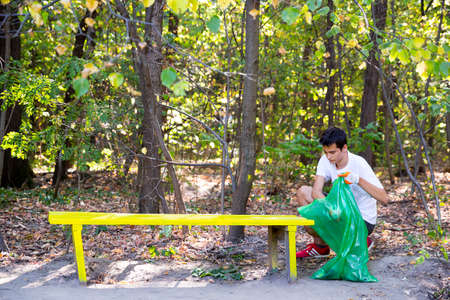 Sofia, Bulgaria - 16 September, 2017: Young man picks up trash in the forest participating in a cleaning campaign. Ecology person cleaning the park.