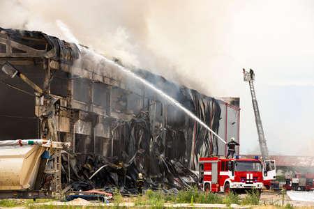 倉庫で火災災害。工業地帯での消火。赤い消防車。