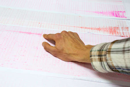 Seismological activity lines on the sheet of measuring paper. Seismological device for measuring earthquakes. Earthquake wave on graph paper. Human finger showing a detail of the earthquake. Stock fotó
