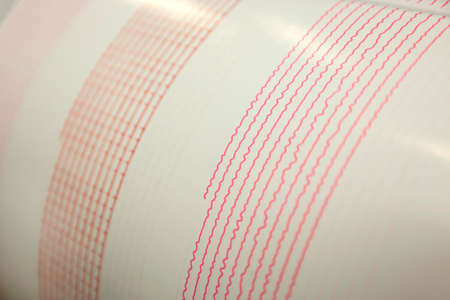 Seismological device for measuring earthquakes. Seismological activity red line on the sheet of measuring paper. Earthquake wave on graph paper.