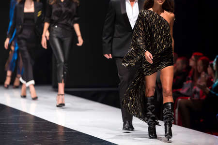 Models walk the runway in different clothes during a Fashion Show. Fashion catwalk event showing new collection of clothes.