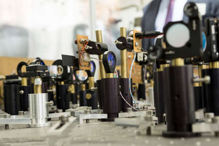 Powerful industrial laser equipment set in a laboratory for physics research. Solid State Physics lab. Light amplification by stimulated emission of radiation (LASER). Stock Photo