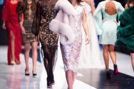 Mannequins femmes défiler la piste dans des robes différentes lors d'un défilé de mode. Défilé de mode montrant la nouvelle collection de vêtements. Dans une rangée. Banque d'images - 94332161