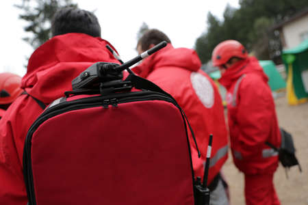 Paramedics from mountain rescue service provide first aid during a training for saving a person in accident. Portable Radio on the backpack. Unrecognizable people.