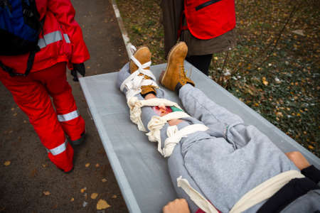 Paramedics from mountain rescue service provide first aid during a training for saving a person in accident with broken leg.
