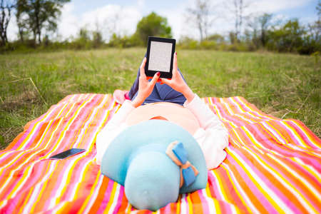 Young woman with blue hat dressed casually uses e-booktablet lying down on a colourful blanket in the park. Modern lifestyle using portable mobile devices everywhere people go. Reading e-mail. Stock Photo