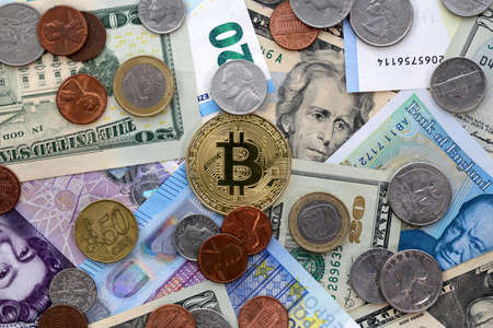 Bitcoin golden coin on United States US twenty dollar bill ($20) and cents, United Kingdom Pound sterling banknotes and EU Euro banknotes.