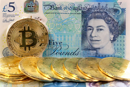 Virtual cryptocurrency money Bitcoin golden coins on United Kingdom Pound sterling banknotes with face of Queen Elizabeth II. Foto de archivo