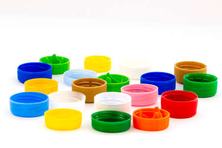 Colorful plastic bottle caps. Studio shot. Plastic waste. Isolated on a white background.