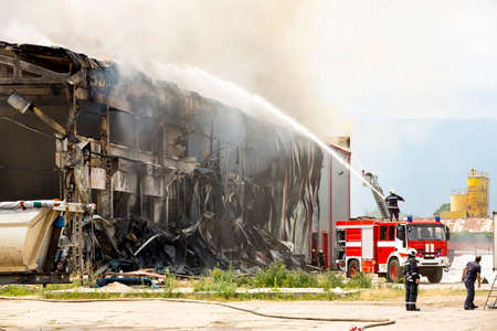 Fire disaster in a warehouse. Fire fighting in an industrial area. Red fire truck. Editorial
