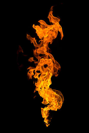 Burning flame isolated on a black background. Fire in red, orange and yellow. Vertical orientation image. Banco de Imagens