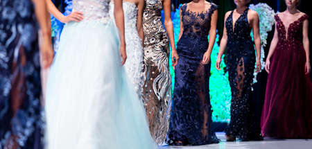 Female models walk the runway in different vivid dresses during a Fashion Show. Fashion catwalk event showing new collection of clothes.