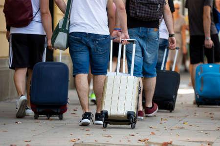 Le persone con le valigie su ruote sono viste di spalle mentre camminano per strada. Persone irriconoscibili.