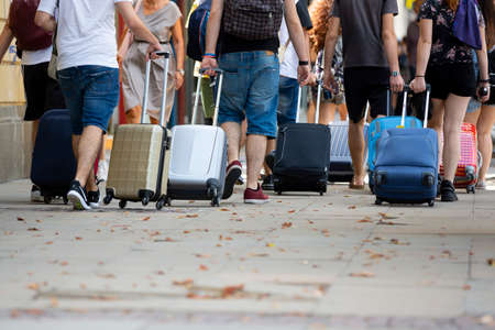 People with suitcases on wheels are seen from their backs on the street walking. Unrecognizable people.