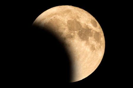 Earth's permanent natural satellite - the Moon during a Lunar eclipse - penumbra. A lunar eclipse occurs when the Moon passes directly behind the Earth. High resolution 6 mp image. On a black background.