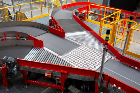 Empty conveyor sorting belt at distribution warehouse. Distribution hub for sorting packages and parcels delivered by air transportation.