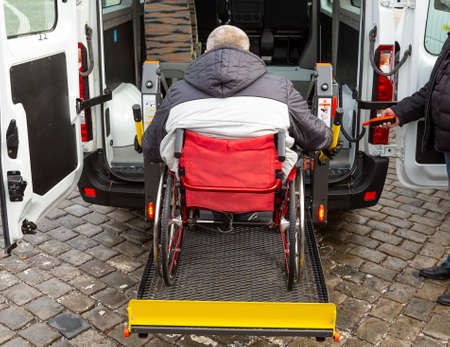 Minibus for handicapped, physically challenged and disabled people in wheelchairs. Minibus with stowed wheelchair ramp. Archivio Fotografico - 115891283