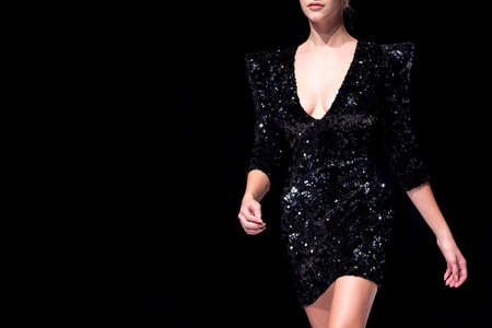 Female model walks the runway in shiny black dress isolated on a black background during a Fashion Show. Fashion catwalk event showing new collection of clothes. Single female model in beautiful dress.