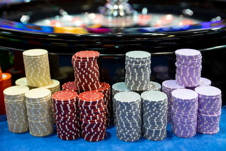 Colourful roulette chips in a casino on a gambling table near roulette wheel. Lots of chips with different nomination and colours. Stock Photo