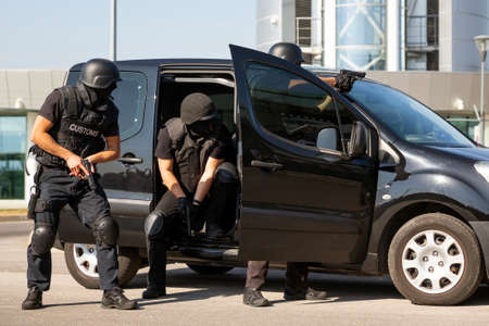 Customs and border protection officers and Drug enforcement administration special forces participate in a training at the airport for searching and seizing of illegal drugs. Unrecognizable people in black.