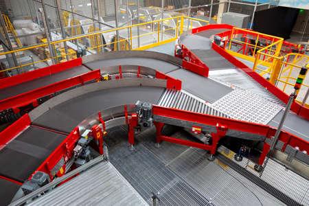 Empty conveyor sorting belt at distribution warehouse. Distribution hub for sorting packages and parcels delivered by air transportation.