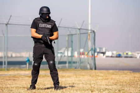 Customs and border protection officer and Drug enforcement administration special force participates in a training at the airport for searching and seizing of illegal drugs. Unrecognizable people in black. 写真素材