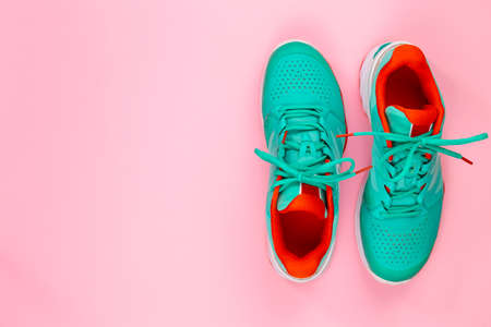 Red, cyan, white pair of new tennis shoes in studio shot over pink background. Directly from above. Imagens