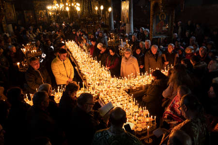 Blagoevgrad, Bulgaria - February 10, 2019: Worshippers light candles on jars with honey during a religious ritual marking the day of Saint Haralampi - the Orthodox patron saint of beekeepers - in the church of the Presentation of the Blessed Virgin. Editorial